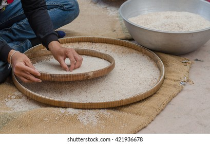 woman competitive winnowing rice by using bamboo basketwork outdoor , soft focus and selective focus