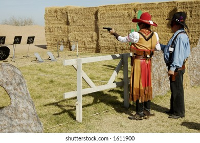 Woman competitor shooting a single-action pistol in a cowboy shoot competition.