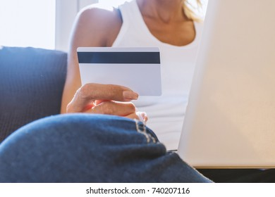 Woman with computer shopping online. Young Woman On Sofa Shopping Online With Debit Card. Hands entering credit card information into a laptop