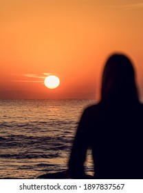 Woman Comtemplating the sunrise in Front of the Sea