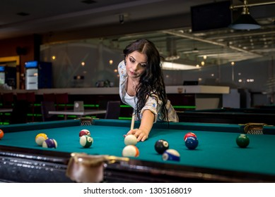 Woman concentrated on billiard game in pub