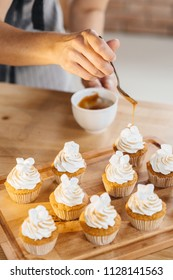woman confectioner pours caramel from a spoon on juicy capcake muffins. Making sweets.
