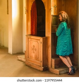 Woman is confessing her sins to the confessor, kneeling at the confessional wearing high heels
