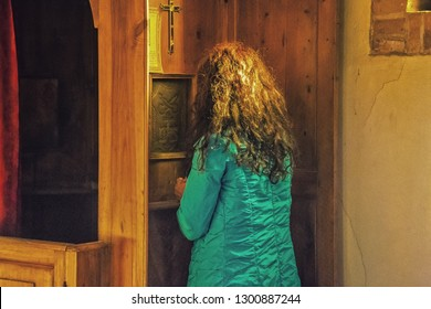 Woman is confessing her sins to the confessor, kneeling at the confessional