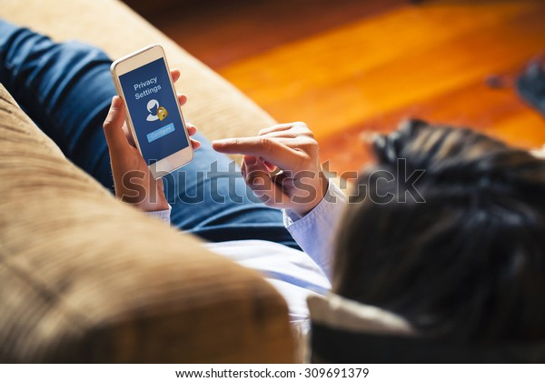 """Woman configuring privacy settings on the mobile phone, lying down at home. Blue screen. """"Privacy settings appears on the screen."""