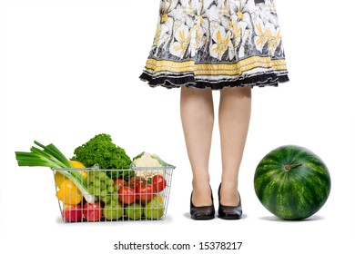 A woman conquers grocery shopping watermelon and a basket full of fresh fruits and veggies.