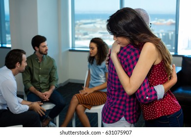 Woman consoling upset colleague at office