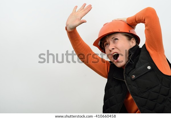 The woman construction in a helmet is frightened danger a threatening from the top and defended stretched arm