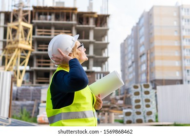 A woman at a construction site in a blue suit, vest and helmet. A middle-aged woman with a project and drawings inspects the construction.