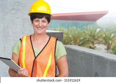 Woman construction worker in hard hat taken outside