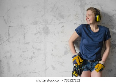 Woman construction worker wearing tool belt. Building, repair concept