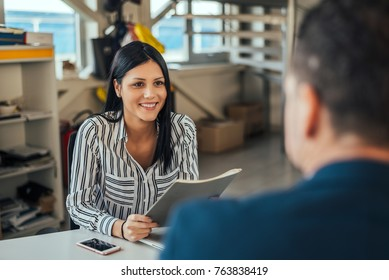 Woman consultant talking with client in office.