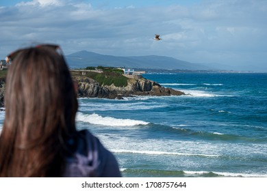 A woman contemplates the flight of a bird at seacoast