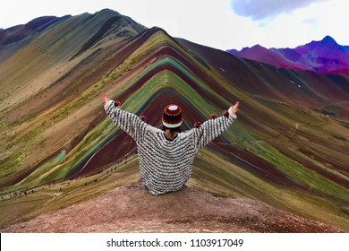 Woman contemplating the view of Rainbow mountain after a long hike.