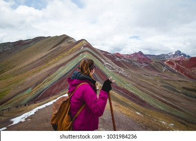 Woman contemplating the view of  Vinicunca (rainbow mountain) after a long hike.