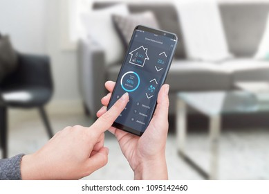 Woman control light in living room interior with smart home control app on modern mobile devices. Living room interior in background.