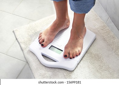 woman controlling her weight on a scale