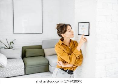 Frauen, die ihr Zuhause mit einem digitalen Touchscreen kontrollieren, der an der Wand im Wohnzimmer angebracht ist