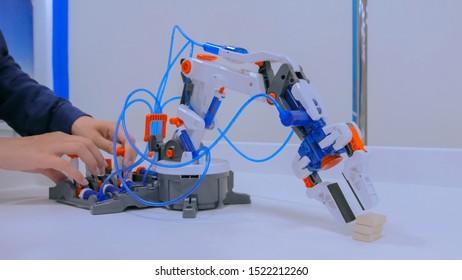 Woman controls robot hand manipulator at technology exhibition. Robotic future concept