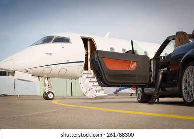 woman convertible car and corporate private jet