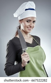 Woman cook in apron and hat holding a chef's knife