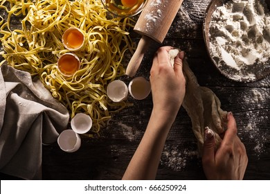 Woman cook hands preparing making tasty homemade classic italian pasta on wooden table. Closeup. Top View. Toning.