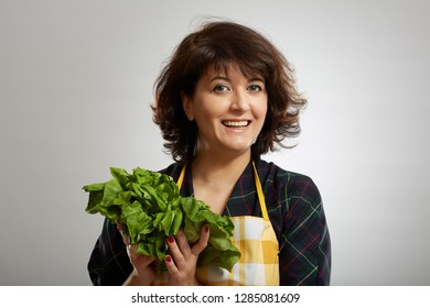Woman cook holding fresh lettuce over gray background