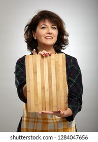 Woman cook holding a wooden board with copyspace