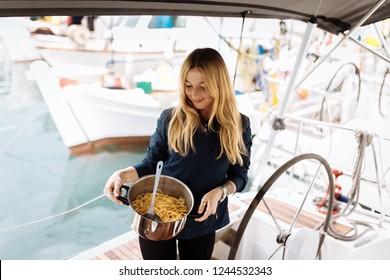 Woman cook italian pasta on boat kitchen. Dinner on yacht. Regatta and sailing race