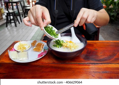 Woman cook porridge for breakfast in the store of one, Asian style food eaten with soft boiled rice