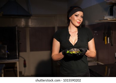woman Cook prepares a burger in the kitchen