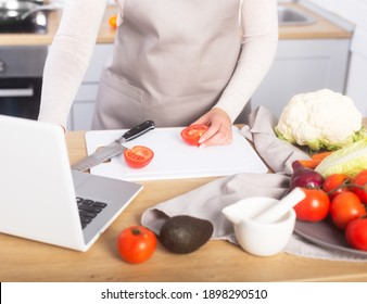 Woman cooking according the tutorial of a online master class