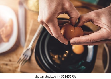 Woman cooking and breaking eggs into the plate in the kitchen at home