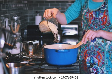 Woman is cooking dinner in a blue cast iron pot, Dutch oven, on a stove