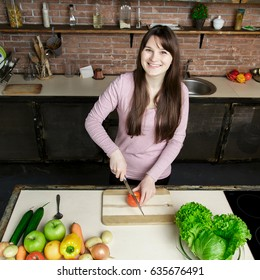 The woman is cooking food in the kitchen. A girl cuts a tomato with a knife. On the kitchen table are fresh vegetables