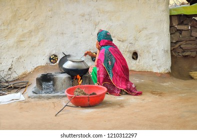 A woman cooking food in a stove made of mud.