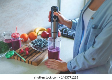 Woman cooking fresh blueberry smoothie with hand blender at kitchen at home. Healthy eating and berry drink