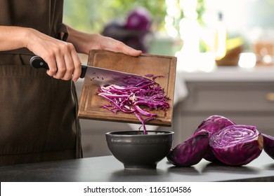 Woman cooking fresh salad with ripe red cabbage at grey table