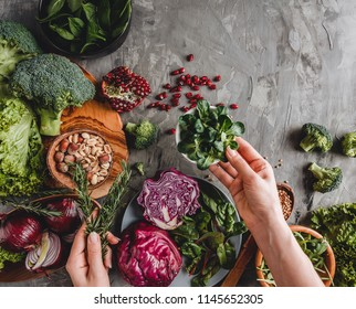 Woman cooking healthy fresh salad with avocado, greens, arugula, spinach in plate over grey background. Healthy vegan food, clean eating, dieting, top view