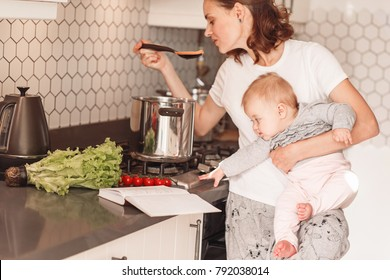 Woman cooking with her little daughter in hands