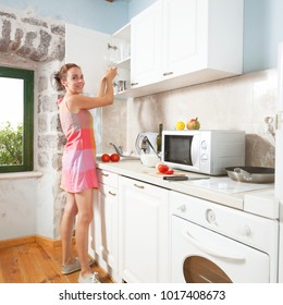 Woman cooking at home. She is preparing salad in her sunny kitchen.