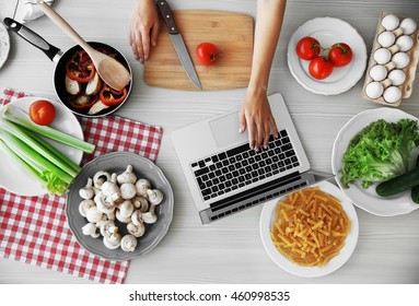Woman cooking in kitchen. Food blog concept, top view