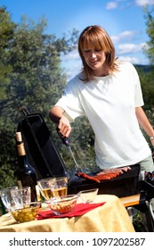 woman cooking meat on a barbecue