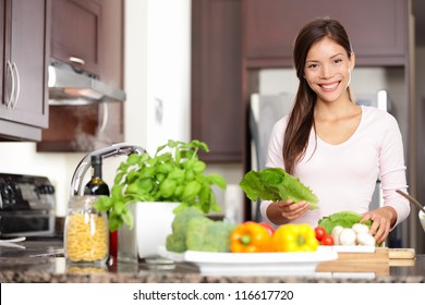 Woman cooking in new kitchen making healthy food with vegetables. Young multicultural Caucasian / Asian Chinese woman in her twenties.