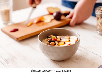 Woman cooking oat porridge. hands cutting fruits in cutting board. Healthy breakfast, oat meal with sliced apple, plum, nectarine and nuts. Bowl of oat flakes on white wooden kitchen table