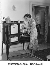 Woman cooking on antique stove