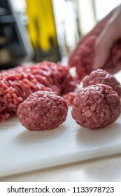 Woman cooking with raw mixed minced meat, half beef, half pork, for burger patty's