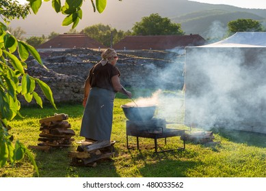 Woman cooking romanian traditional food on fire outdoor in a camping holiday of ulpia traiana, sarmisegetusa, hateg, hunedoara, romania in summer season