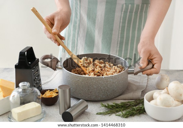 Woman cooking tasty risotto at table