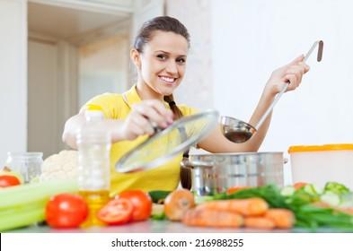 woman cooking  vegetarian food in saucepan at home kitchen